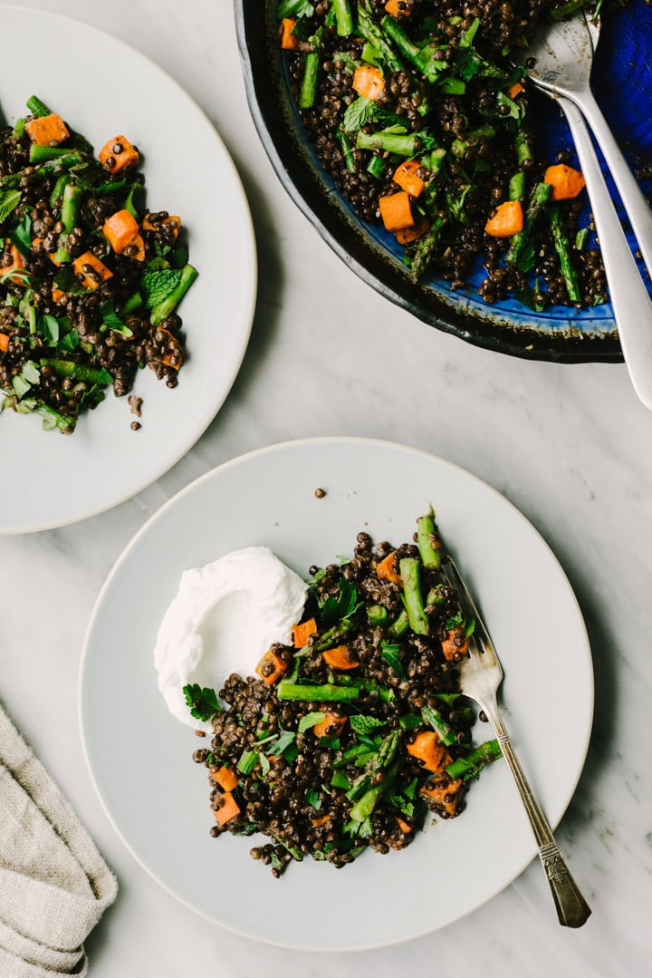 Two plates of cooked black lentils tossed with roasted carrots and asparagus.