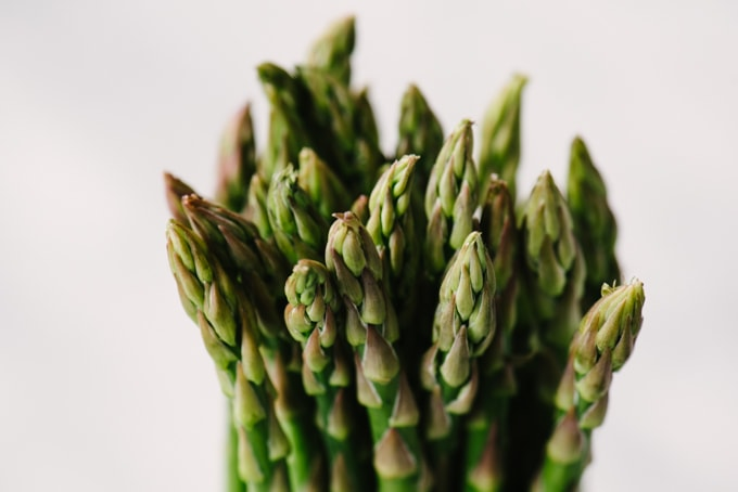 A close-up image of fresh asparagus tips with tightly packed florets.