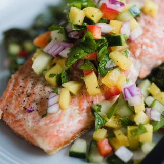 This healthy, colorful cucumber mango salsa is one of my favorite toppings for simple pan-seared wild salmon. It's crunch, tangy, slightly tweet, and perfectly tart. This a fast and easy whole30 recipe that's ready in just 20 minutes! Get the recipe, plus my tips for restaurant perfect seared salmon every single time. Simple and healthy has never tasted so good.