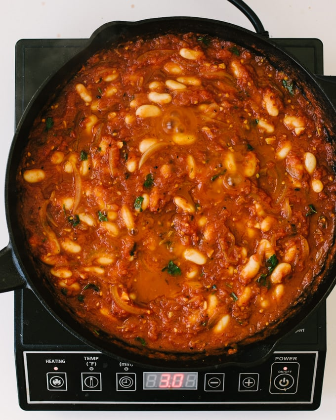 An overhead view of white bean tomato sauce for eggs in purgatory in a cast iron skillet resting on a tabletop burner.
