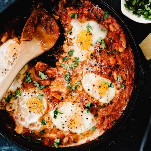 Gluten free white bean eggs in purgatory in a cast iron skillet with herbs and parmesan cheese on the side.