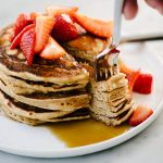 A stack of whole grain pancakes topped with macerated strawberries.