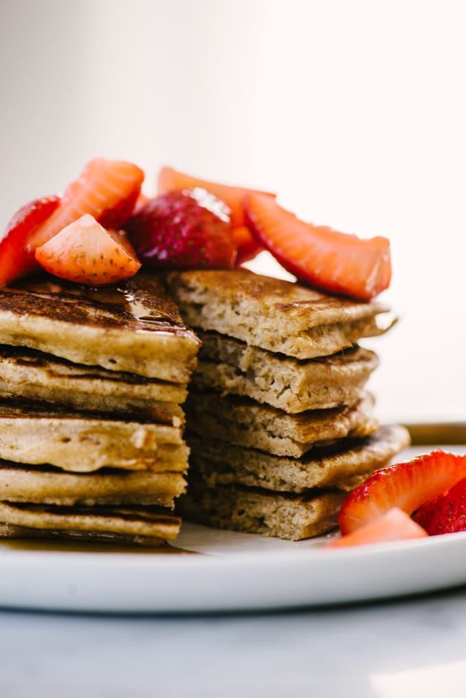 A close up image of a stack of whole grain pancakes with a bite removed, showing the rich fluffy interior.