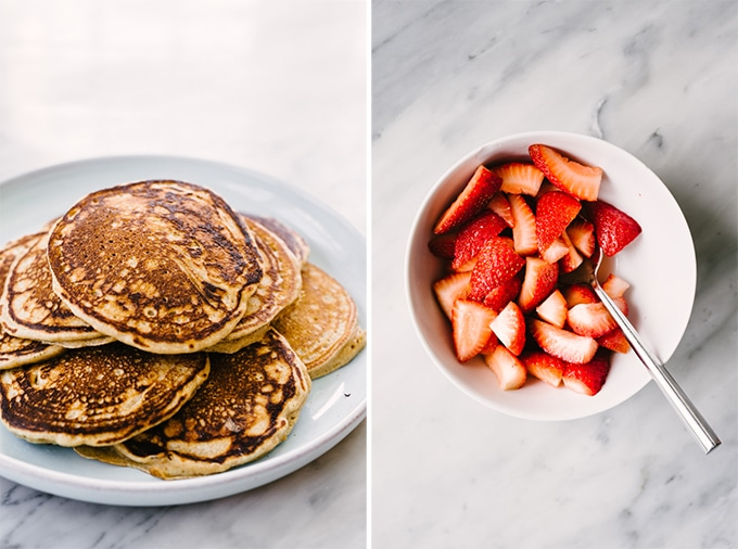 Left - whole grain pancakes piled onto a blue platter. Right - a bowl of macerated strawberries to top the pancakes.