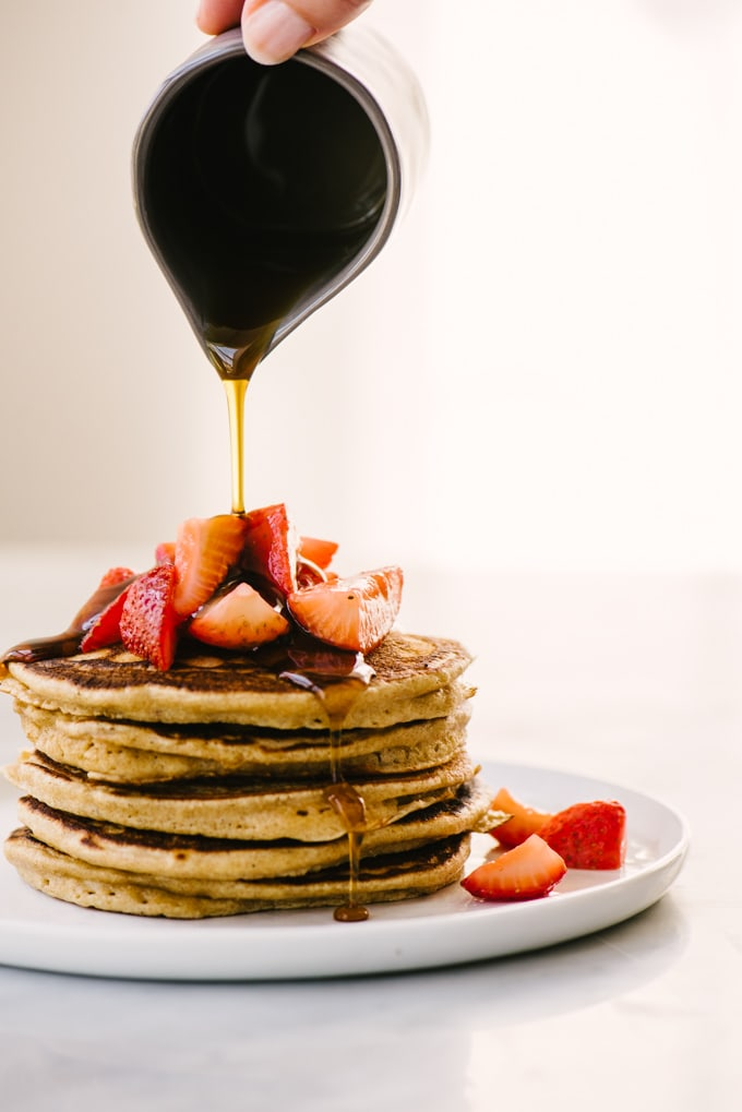 A woman pouring maple syrup from a small pitcher onto a stack of whole grain pancakes topped with macerated strawberries.