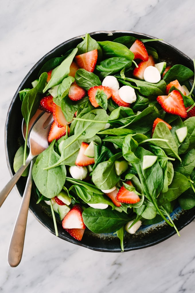 A large salad bowl filled with the base for strawberry chicken salad on a marble table.