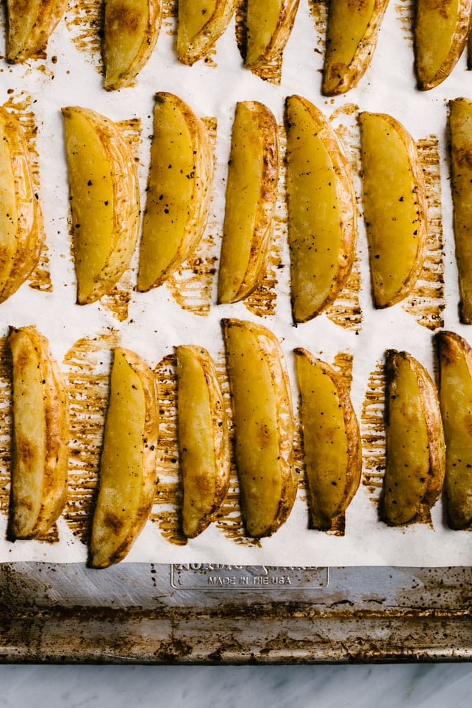 A baking sheet of crispy baked potato fries fresh from the oven.