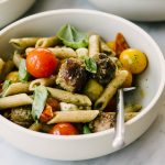 A bowl of caprese pasta tossed with Italian sausage and clean basil pesto on a marble table.