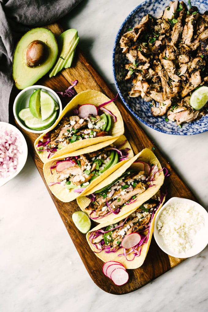 Four grilled chicken tacos arranged on a wood serving platter with red cabbage, avocado, queso fresco, red onion, and a bowl of cilantro lime chicken on the side.