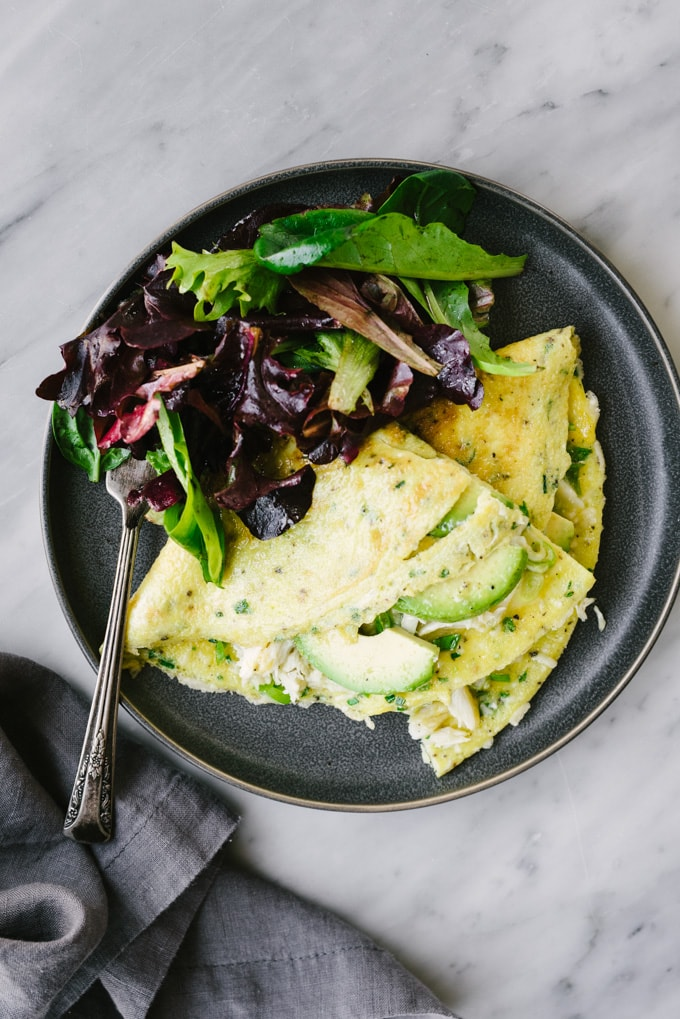 A three egg crab omelet with avocado and fresh herbs on a grey plate with a side green salad.