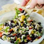 A woman dipping a tortilla chip into a bowl of black bean salsa with mango and lump crab meat.