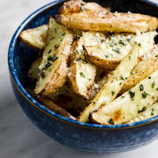 A bowl of crispy oven baked basil fries in a blue bowl on a marble table.