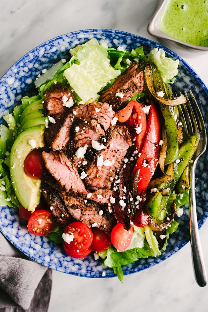 A paleo and whole30 friendly steak fajita salad in a blue salad bowl with grilled peppers and onions, avocado, and tomatoes and cilantro lime dressing on the side.