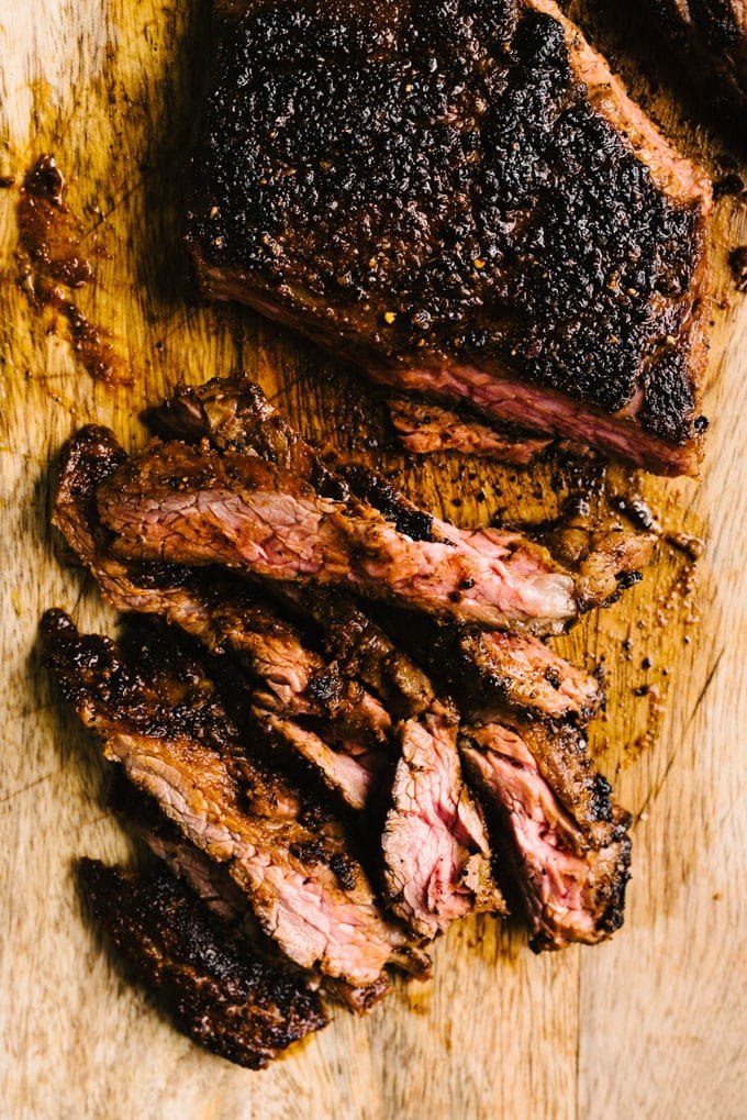 Thinly sliced grilled skirt steak seasoned with fajita dry rub spices on a wood cutting board.