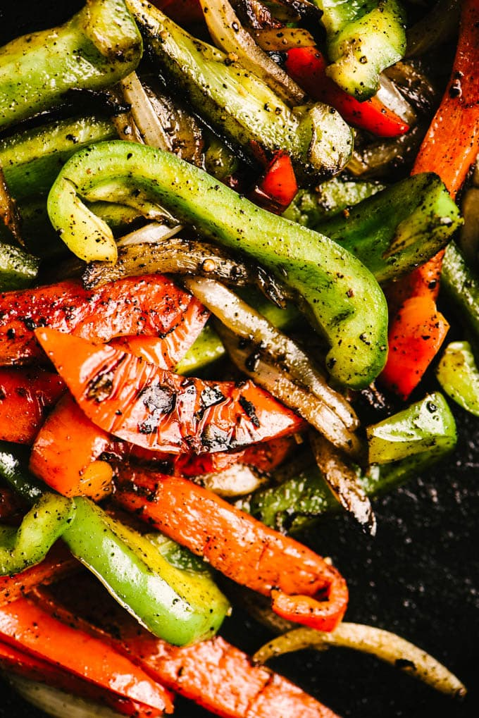 Charred red and green bell peppers and sweet onions in a cast iron skillet.