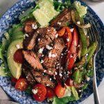 A bowl of steak fajita salad with sautéed peppers and onions, avocado, and a side of cilantro vinaigrette.
