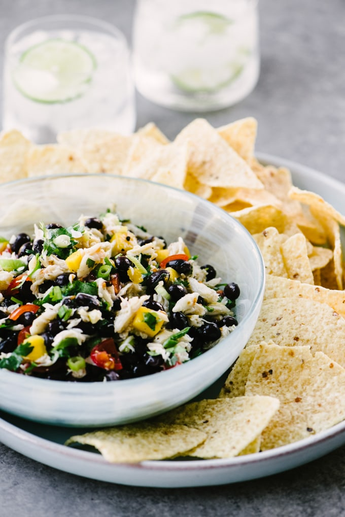 A small blue bowl of black bean salsa with crab and mango on a blue platter with yellow corn tortilla chips.