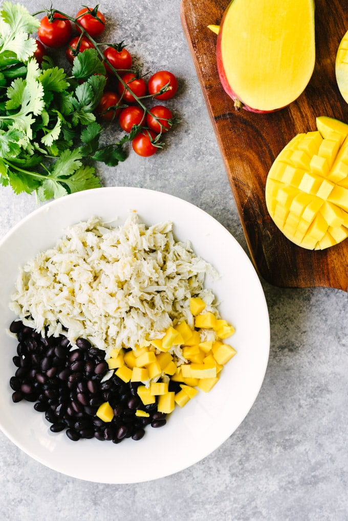A bowl filled with lump crab meat, black beans, and diced mango with whole cherry tomatoes and cilantro in the background.