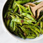 A recipe for sugar snap peas cooked with bacon, mint, and lemon in a large serve bowl with wooden serving utensils.