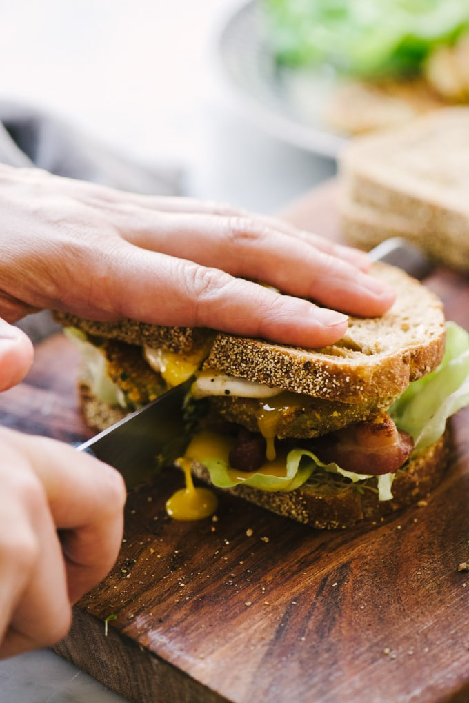 A woman's hand slicing a fried green tomato BLT sandwich in half.