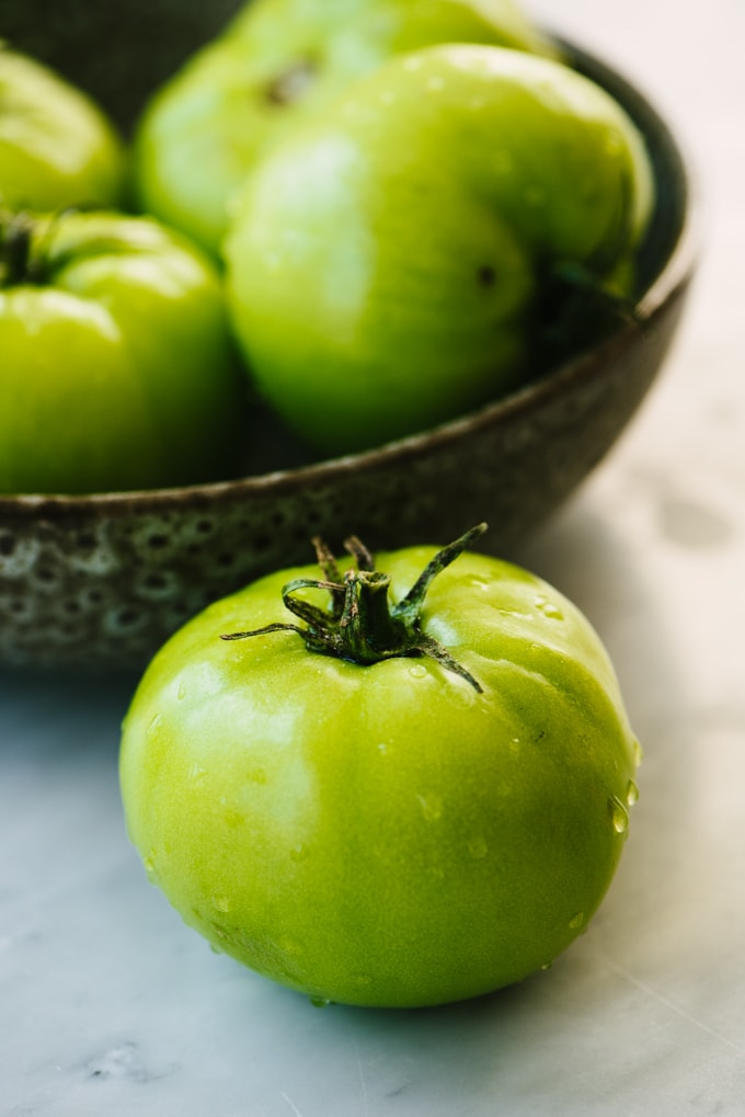 A single whole green tomato in front of a brown ceramic bowl filled with additional green tomatoes.