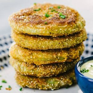 A stack of fried green tomatoes battered in cornmeal, oat flour, and buttermilk with a side of dipping sauce.