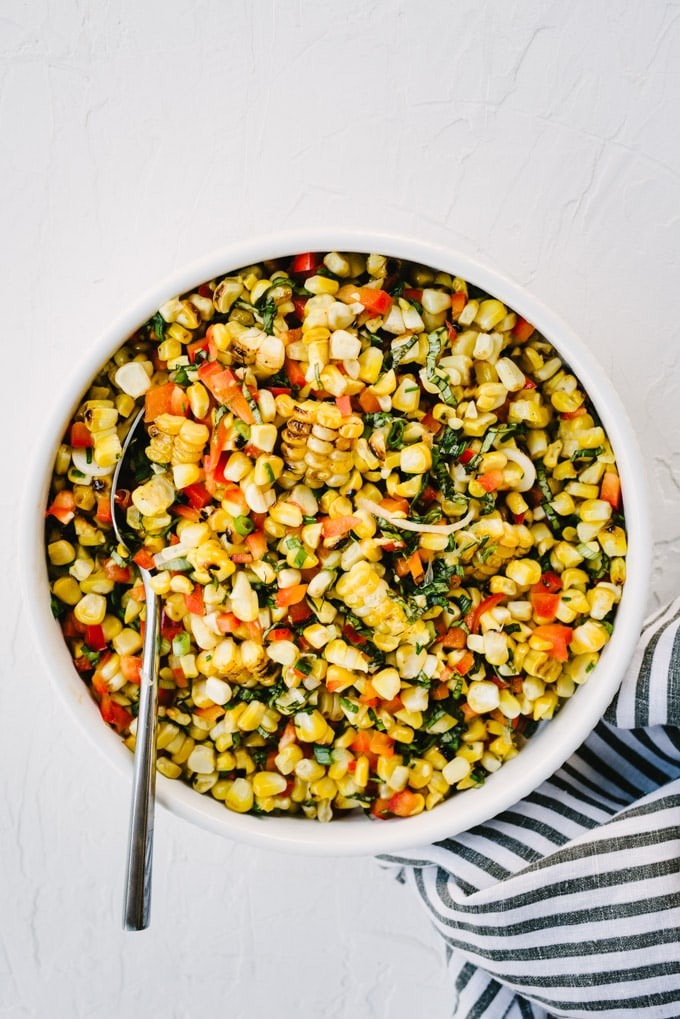 A bowl of simple grilled corn salad with lime, bell pepper, green onions, and basil on a marble table with a grey and white striped napkin.
