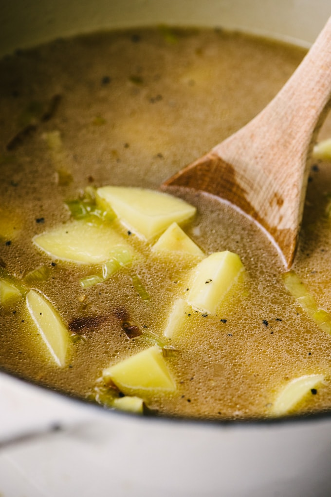 Chunks of diced potato with leeks and bone broth in a dutch oven.