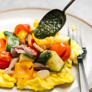 Whole30 pesto sauce being drizzled over scrambled eggs topped with roasted vegetables.