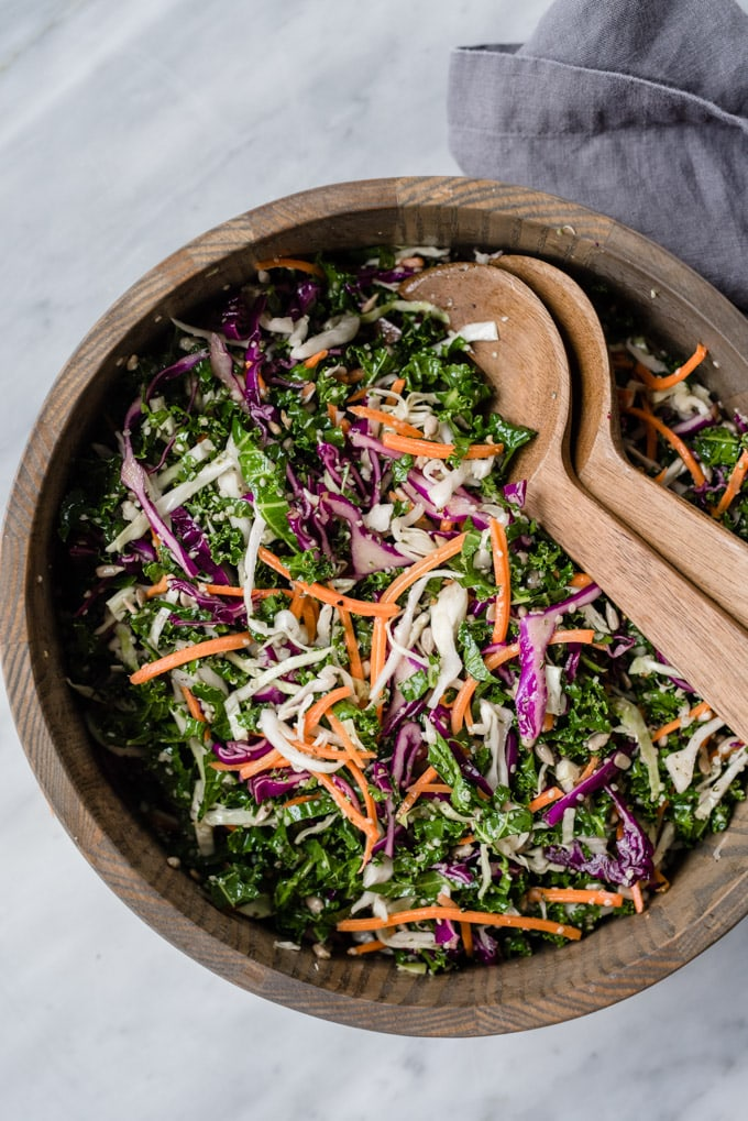 Crunchy kale slaw (or salad) tossed with red and green cabbage, carrots, hemp seeds, and sunflower seeds in a wood serving bowl.