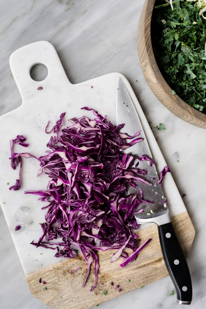 Thinly sliced red cabbage on a marble cutting board for kale slaw.