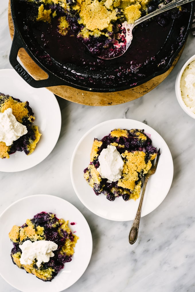 Three servings of cast iron skillet cooked blueberry cobbler topped with homemade whipped cream.