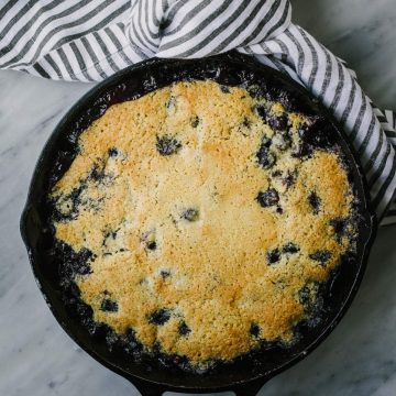Gluten free blueberry cobbler cooked in a cast iron skillet on a marble table with a striped kitchen towel.
