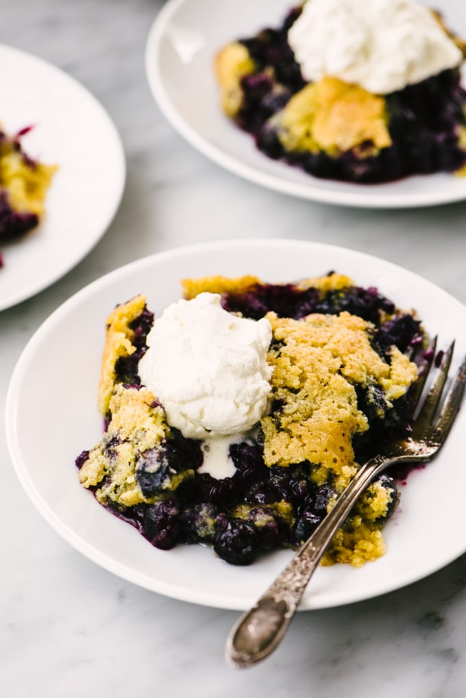 A serving of gluten free blueberry cobbler on a small white plate topped with homemade whipped cream.