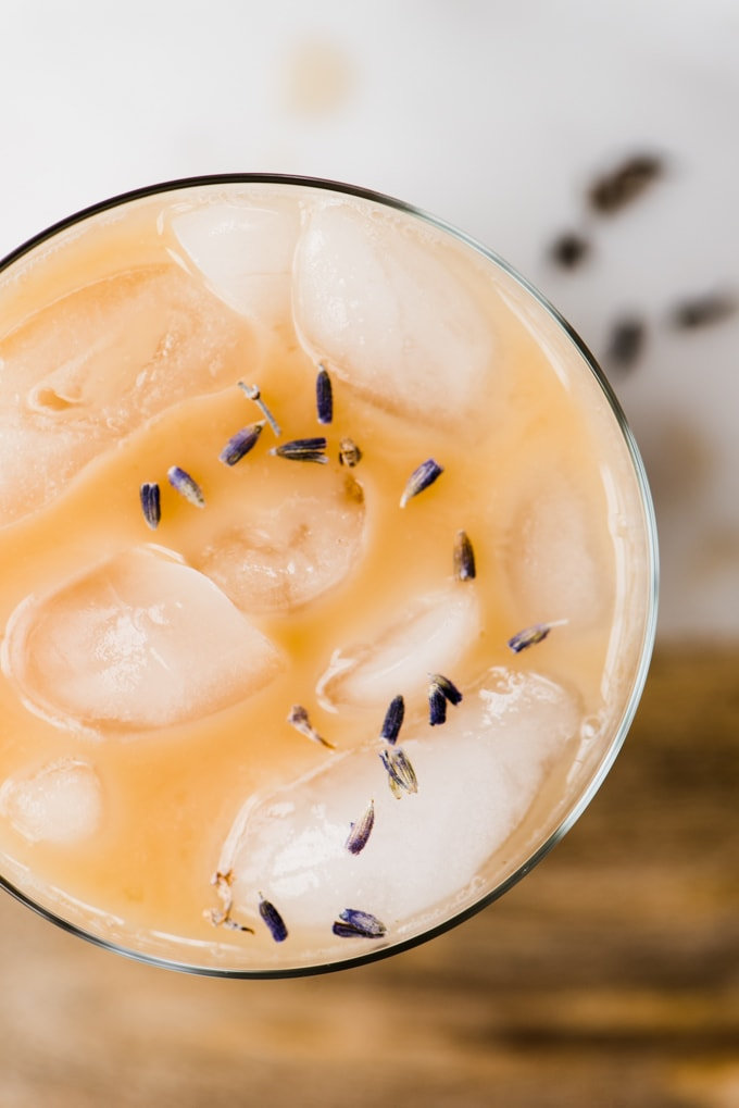 An overhead view of an iced london fog latte garnished with lavender leaves. A healthy, sugar free, dairy free ice tea latte recipe!