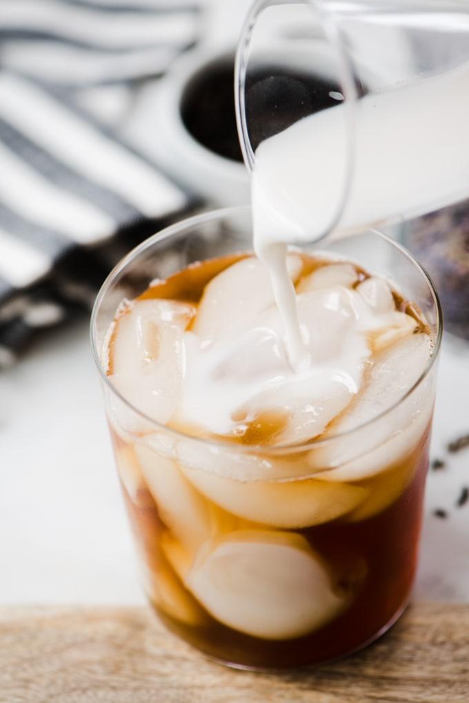 Pouring cashew milk or almond milk into an iced london fog tea latte.