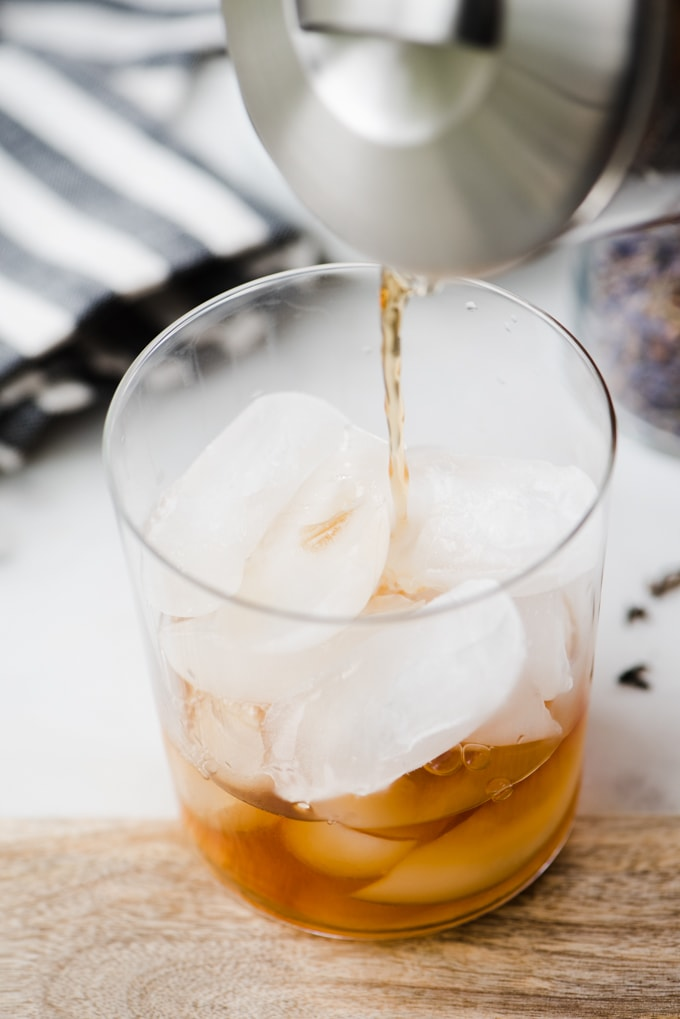 A woman pouring earl grey tea brewed with lavender into a glass of ice for a refreshing paleo london fog latte recipe.