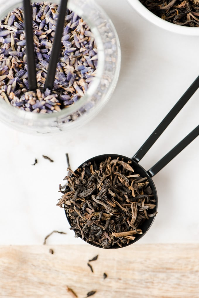 A tablespoon of loose leaf earl grey tea next to a small jar of lavender leaves for a london fog tea latte recipe.