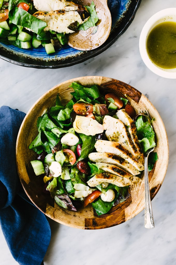 A wood bowl with a serving of mediterranean chicken salad with grilled herb lemon chicken, artichoke hearts, olives, tomatoes, cucumbers, fresh mozzarella, and oregano vinaigrette.