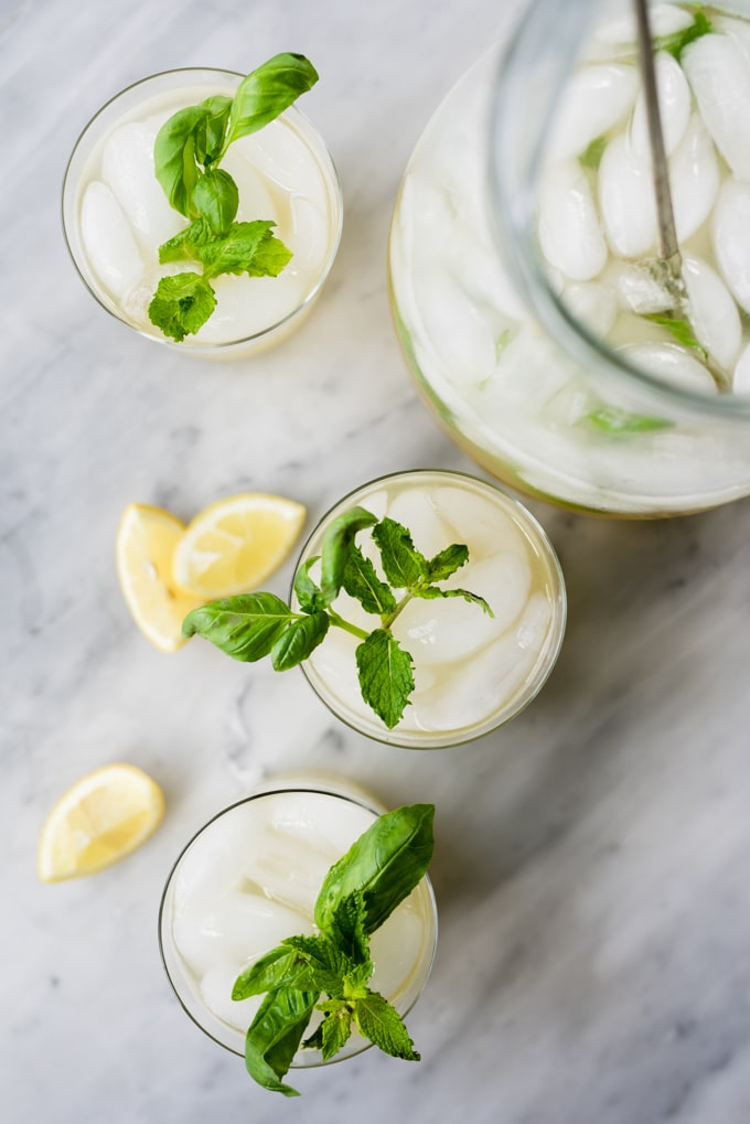A pitcher of mint and basil lemonade with three full glasses garnished with fresh herbs and lemon wedges.