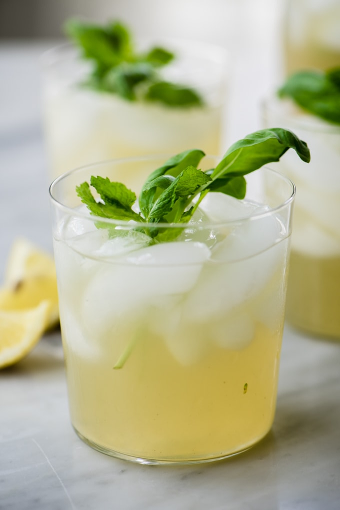 Three glasses of paleo mint and basil lemonade made with fresh squeezed lemons and sugar free honey simple syrup.