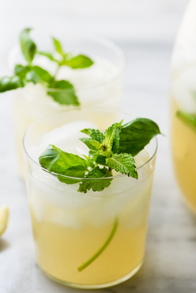 A glass of refreshing, paleo mint and basil lemonade made with honey and garnished with fresh herbs.