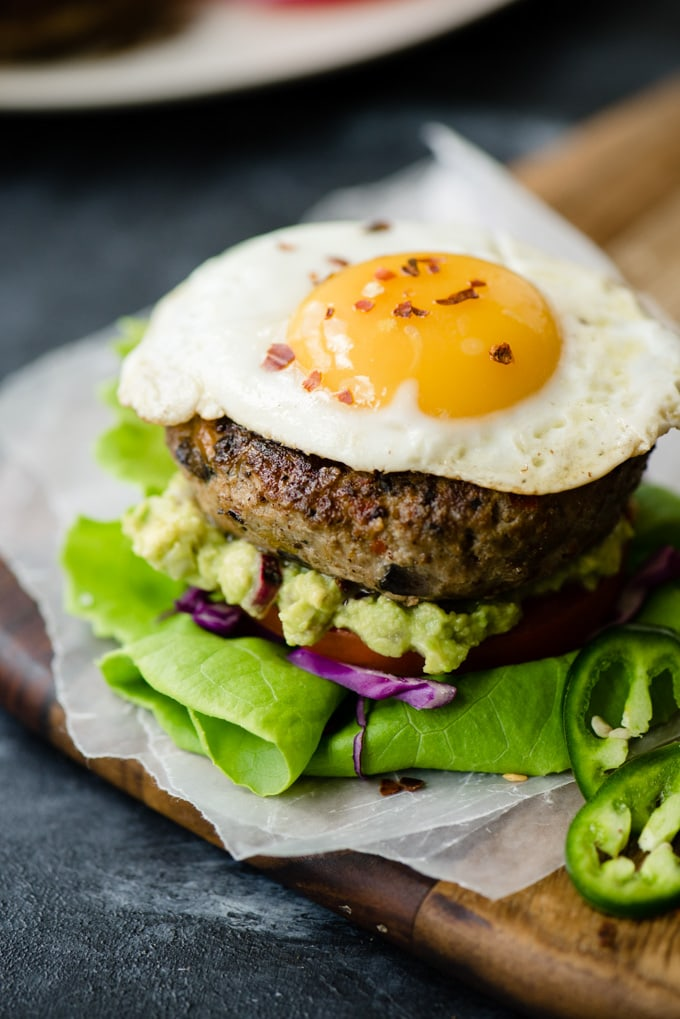 Keto and paleo turkey burger on a bed of lettuce, onion, and tomato with a serving of guacamole and topped with a fried egg.