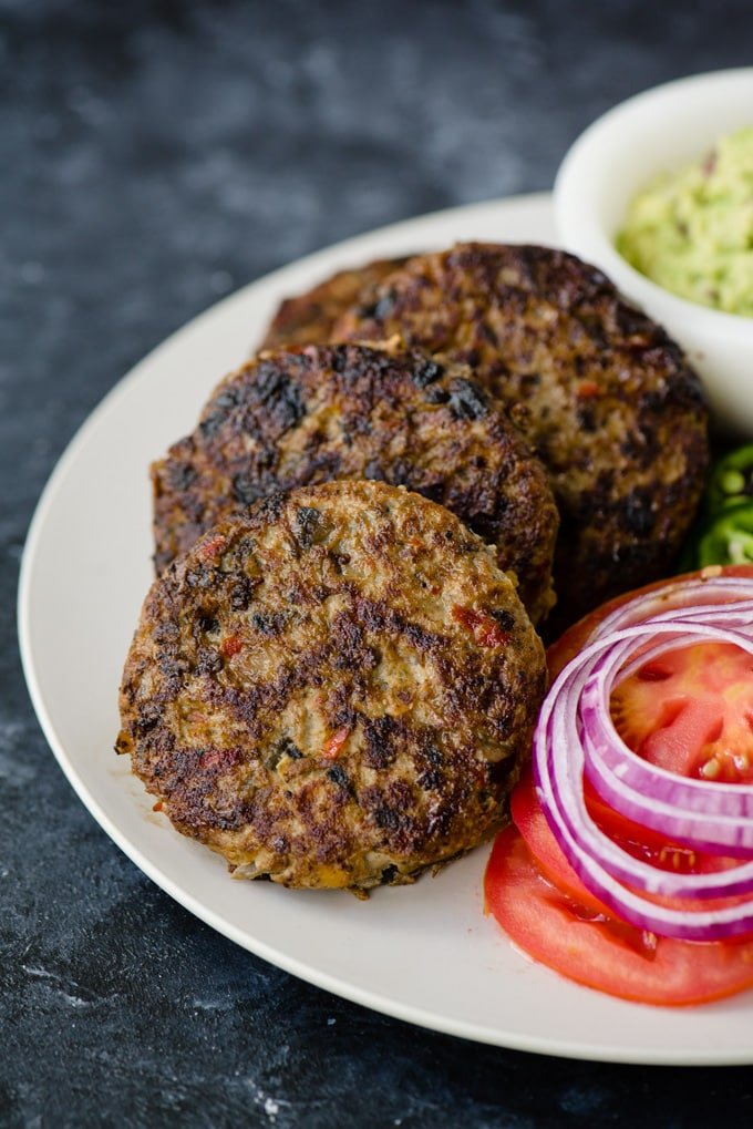 Paleo turkey burgers on a platter with slices of lettuce and tomato, and a small bowl of guacamole.