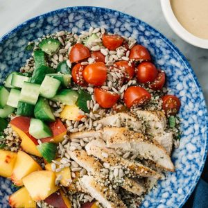 Crunchy summer quinoa salad in a blue bowl with chicken, peaches, cucumbers, tomatoes, sunflower seeds, hemp seeds, and a creamy sunbutter dressing.