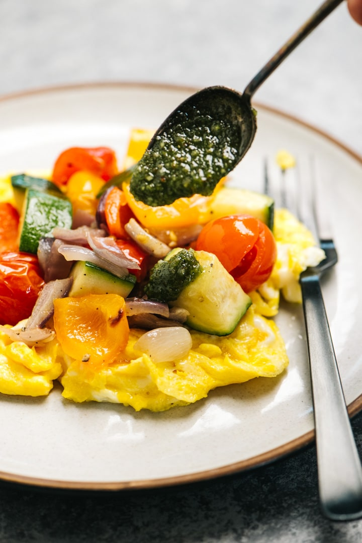 Dairy free pesto sauce being drizzled over scrambled eggs topped with roasted vegetables.