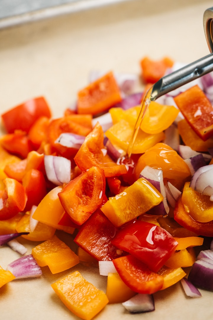 Diced peppers and onions on a parchment lined baking sheet.