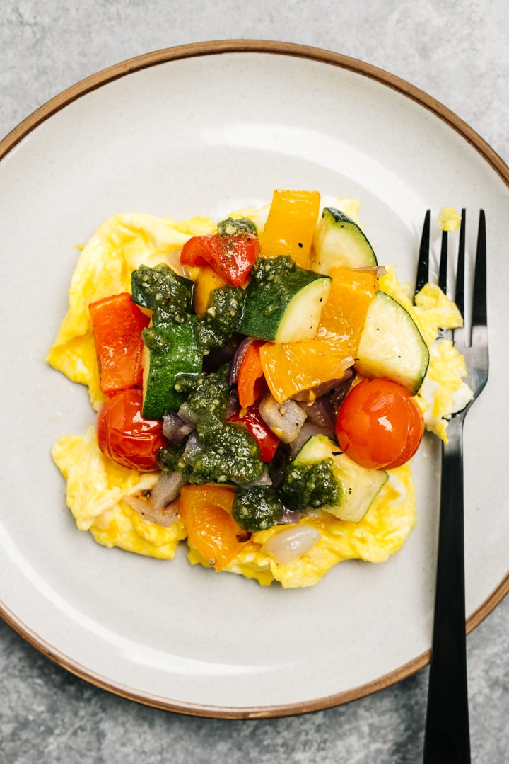 Scrambled eggs with roasted vegetables and pesto sauce on a cream ceramic plate.