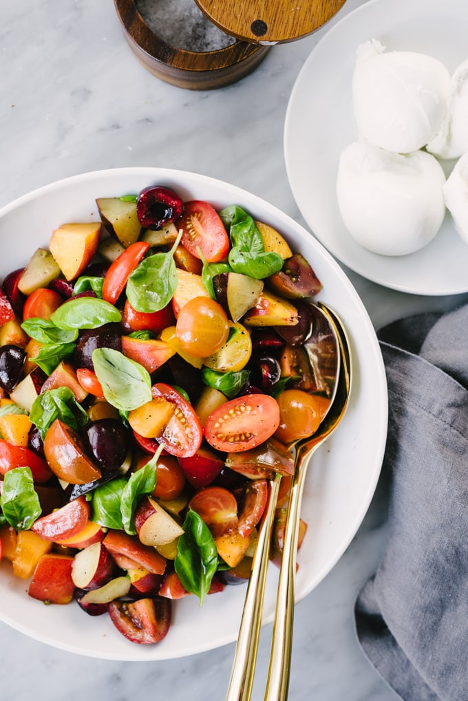 A bowl of stone fruit salad with tomatoes and a small dish of fresh burrata on the side.