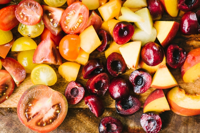 Diced peaches, nectarines, pears, plums, cherries and tomatoes on a cutting board for stone fruit salad.